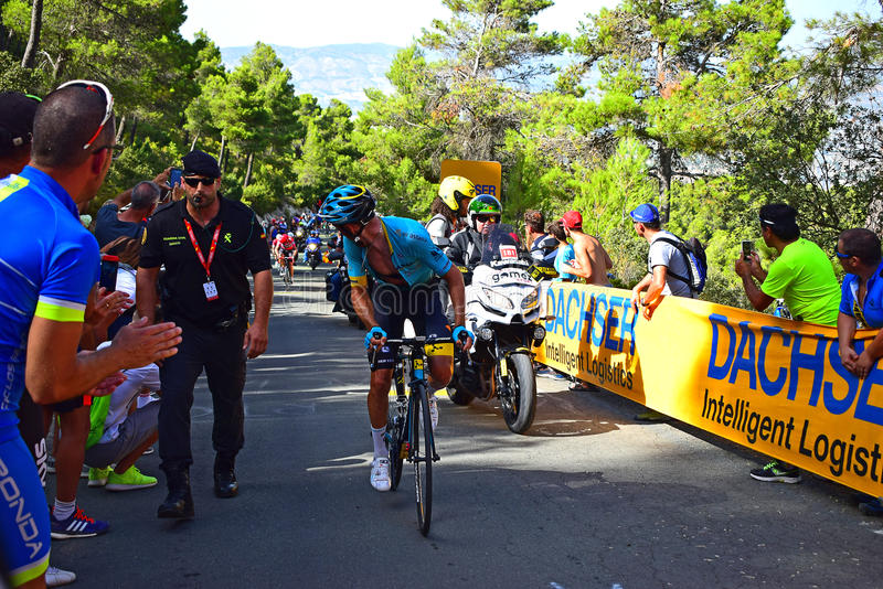 A Cycle Racer Looking Behind La Vuelta España Cycle Race. A Guardia Civil police officer controls the crowd for the rider near the mountain top finish in the stock image