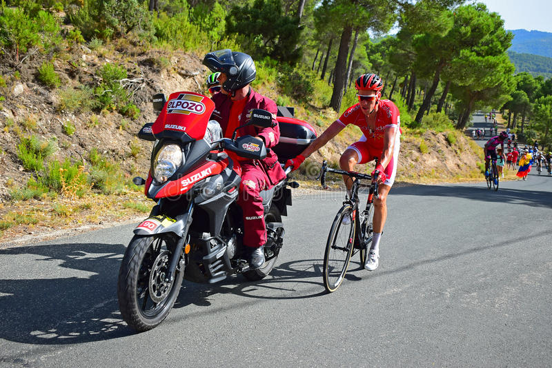 Cycle Racing Holding On To Motorcycle La Vuelta España. A couple of riders get a tow behind a motorcycle at the end of stage eight Xorret De Cati in the 2017 stock images