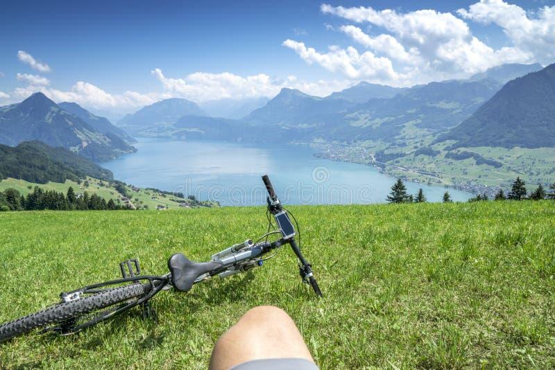Cycler détend sur la luzerne de lac photographie stock