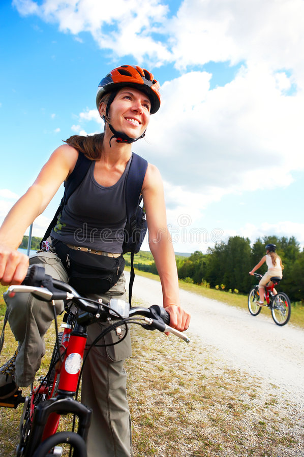 Cycling. Young smiling woman cycling in the park stock images