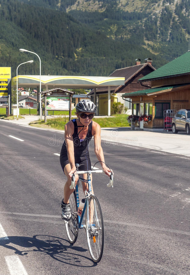 Cycling circulating in the austrian roads. Austrian cyclist circulating gossen roads on a sunny day. It is an editorial image vertically royalty free stock image