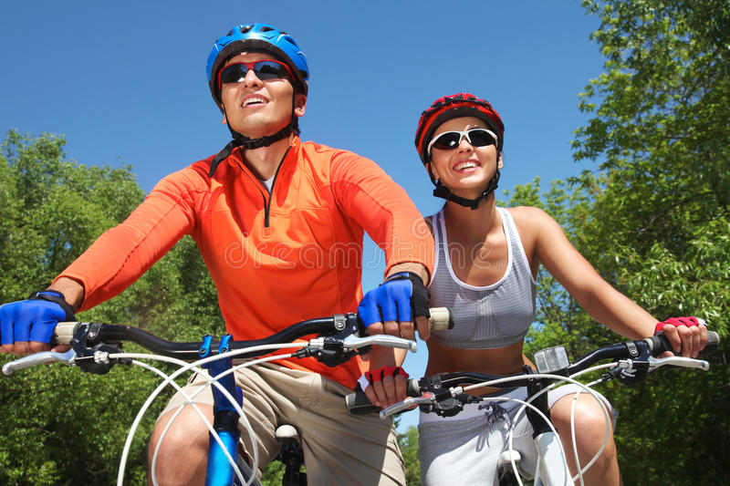 Cycling couple. Young smiling couple cycling through summer park