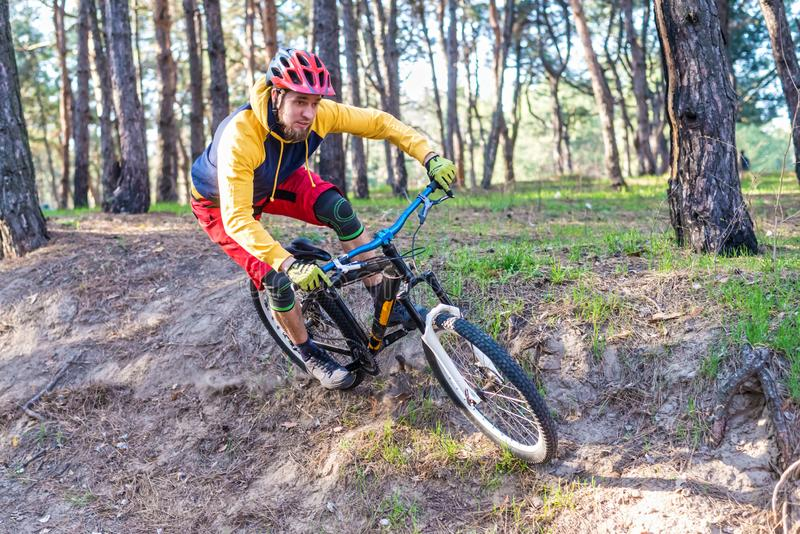 Cycling, a cyclist in bright clothes riding a mountain bike on the edge of a cliff. Active lifestyle. Enduro competition action activity athlete bicycle biker stock photo