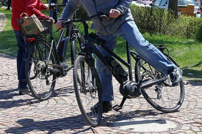 Cycling and getting off an e-bike can be dangerous for seniors royalty free stock image