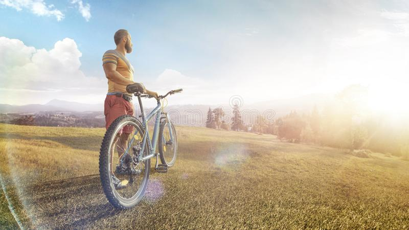 Cycling. Man with bike on a forest road in the mountains on a summer day. Mountain valley during sunrise. Sport. Cycling. Man with bike on a forest road in the stock image