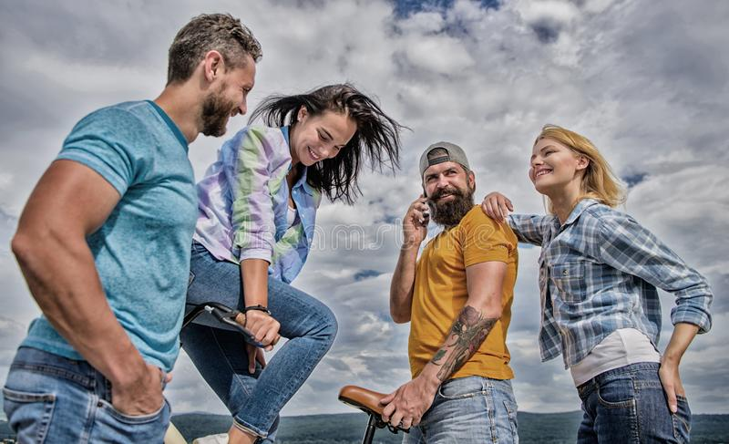 Cycling modernity and national culture. Double date concept. Group friends hang out with bicycle. Company stylish young. People spend leisure outdoors sky royalty free stock photography