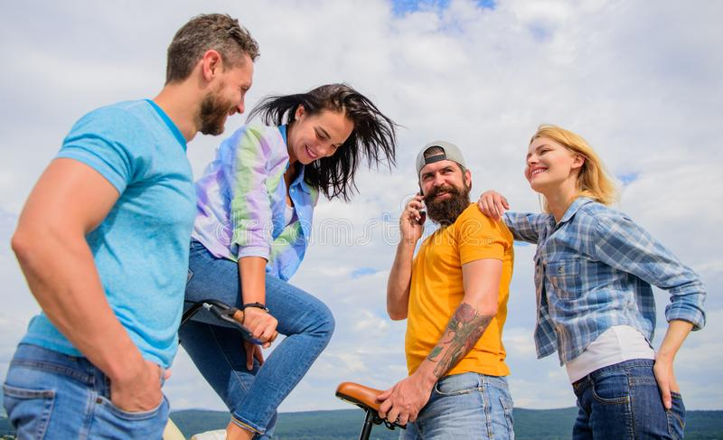 Cycling modernity and national culture. Double date concept. Group friends hang out with bicycle. Company stylish young. People spend leisure outdoors sky royalty free stock images