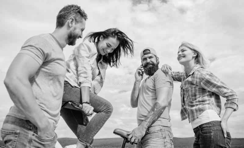 Cycling modernity and national culture. Double date concept. Group friends hang out with bicycle. Company stylish young. People spend leisure outdoors sky royalty free stock photo