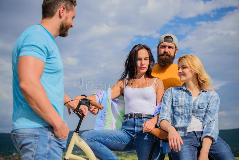 Cycling modernity and national culture. Group friends hang out with bicycle. Company stylish young people spend leisure. Outdoors sky background. Bicycle as stock photo