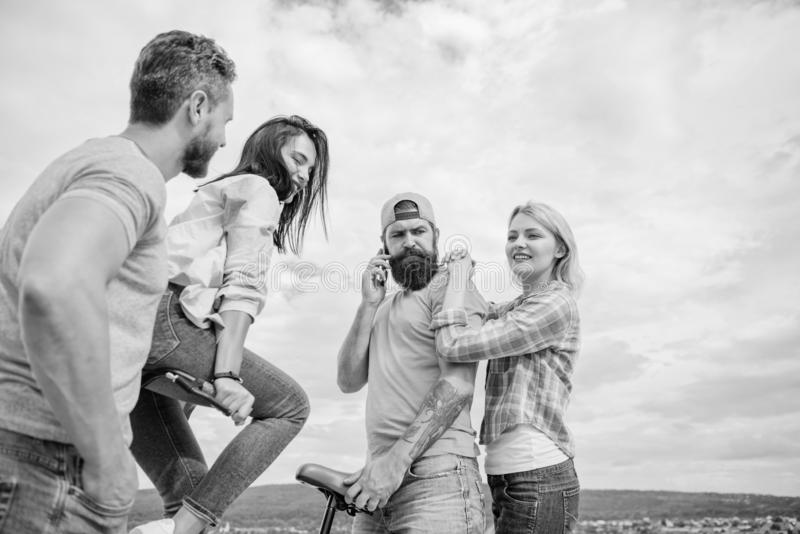 Cycling modernity and national culture. Group friends hang out with bicycle. Company stylish young people spend leisure. Outdoors sky background. Couple meet stock photography