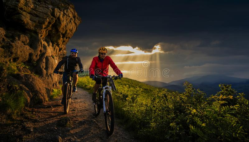 Cycling, mountain biker couple on cycle trail in autumn forest. Mountain biking in autumn landscape forest. Man and woman cycling stock photo