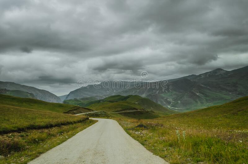 Cycling mountain road. Misty mountain road in high mountains.. Cloudy sky with mountain road stock photo