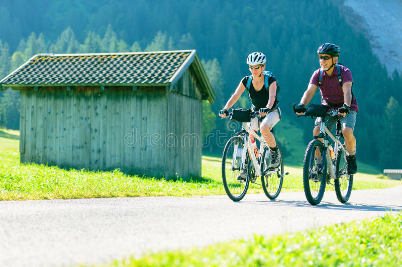 Cycling Senior Couple. Enjoying summer at the vilsalpsee in austria royalty free stock image