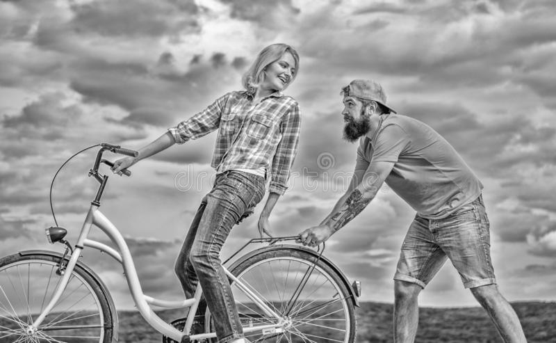 Cycling service. Service and assistance. Mechanic helps maintain bicycle. Supportive service. Woman rides bicycle sky. Background. Man helps keep balance ride stock images