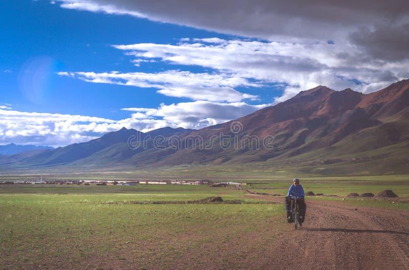 Cycling on tibetan plateau royalty free stock image