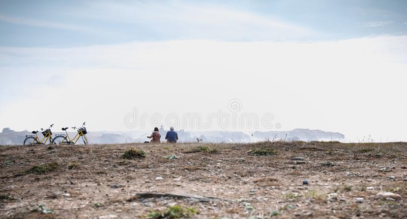 Cycling tourists taking a break by the sea reading a map in Yeu Island. Port Joinville on the island of Yeu, France - September 18, 2018: Cycling tourists taking royalty free stock photo