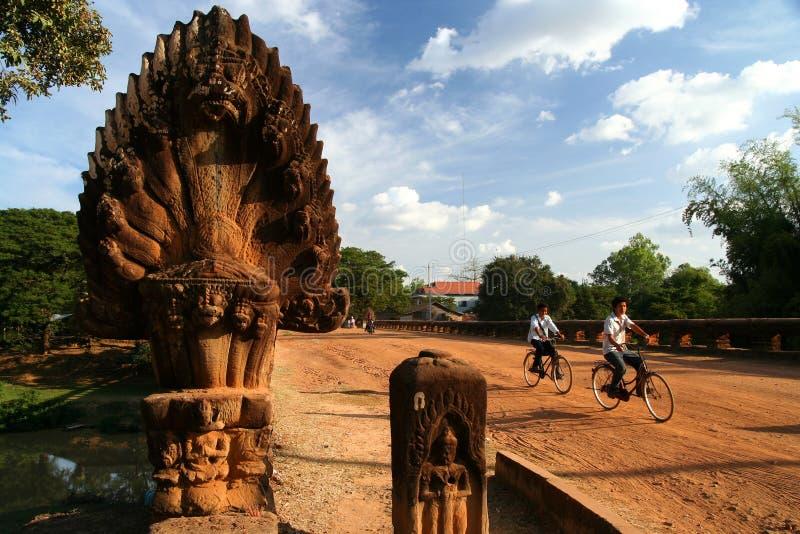 Cycling towards Angkor. Kids cycling over a bridge from an Angkor Wat period, Cambodia stock photos