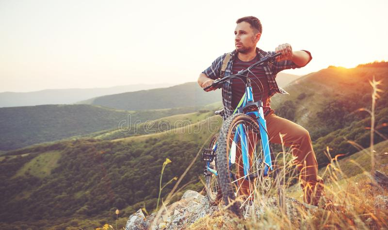 Cycling. young man with bicycle on nature in mountains stock photo