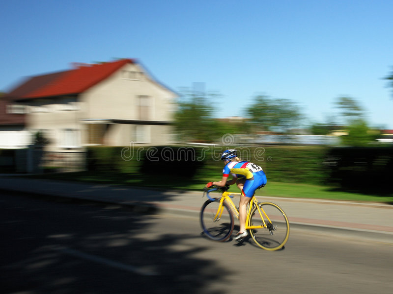 Cyclist. A cyclist speeds through a neighborhood. His surroundings are blurred showing his speed and motion