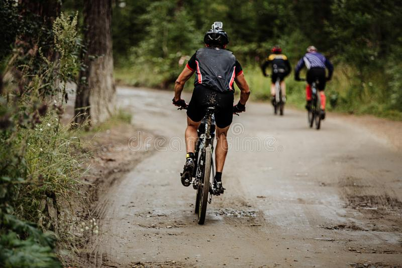 Cyclist with action camera on helmet. Biking in group on forest trail royalty free stock photos