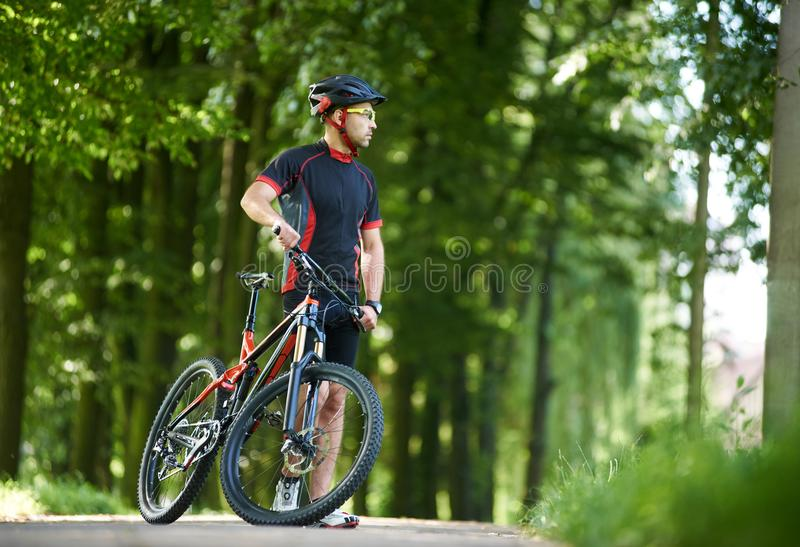 Cyclist admiring nature in green park. Man professional cyclist in cycling clothing and helmet looking away in distance, taking break from riding on bicycle in royalty free stock photos
