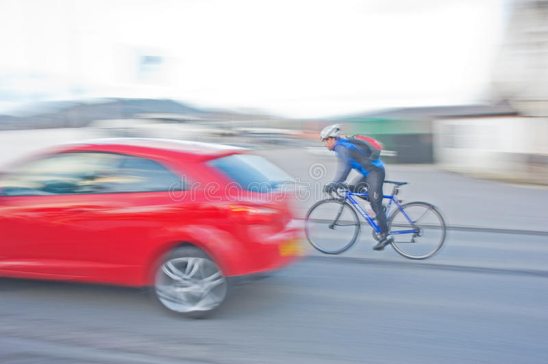 Cyclist on Alpina bike overtaking car. A panned image showing a cyclist on an Alpina bike overtaking a red saloon car at Muirtown Marina Inverness, Scotland royalty free stock images