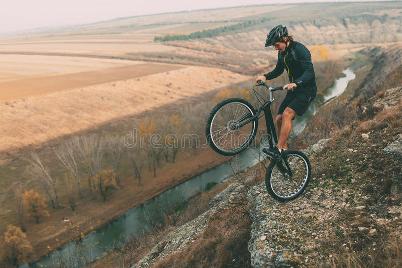 Cyclist balancing on edge stock images
