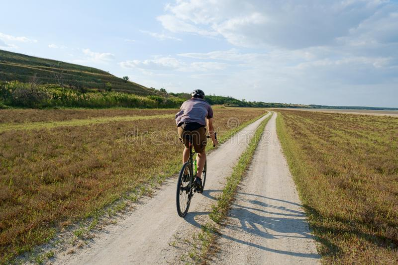 Cyclist bicycle biker in safety helmet ride high speed landscape royalty free stock photos