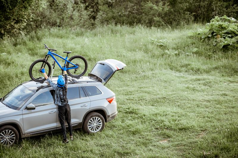 Cyclist with bicycle and car outdoors royalty free stock image
