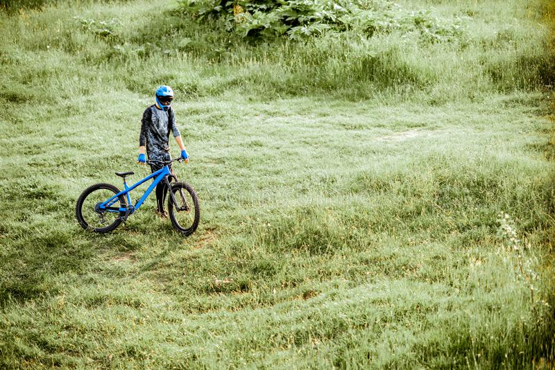 Cyclist with bicycle on the green meadow stock photo