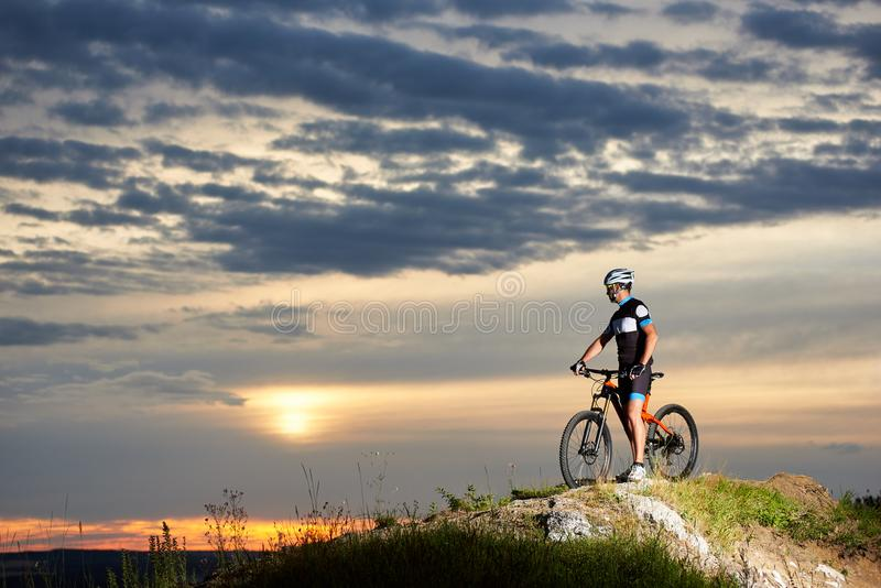 Cyclist with bicycle rests on cliff top in mountains enjoying sun at sunset under an unusual sky stock photo