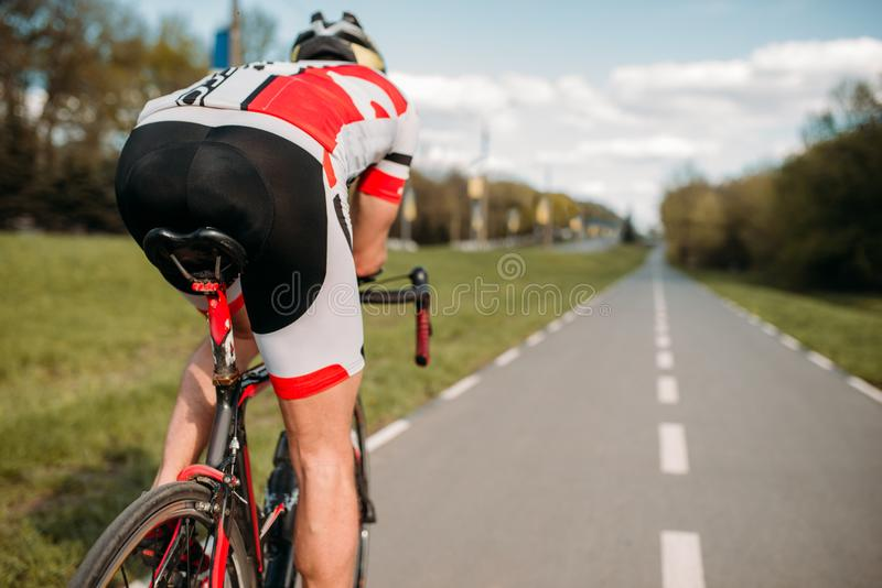Cyclist on bike path, view from the rear wheel stock photography