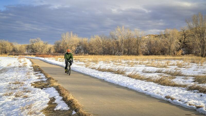 Cyclist on a bike trail in winter scenery royalty free stock images