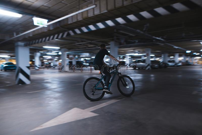 Cyclist on a blue bike rides on a speed under an underground car park stock image