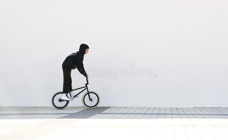 Cyclist bmx against a white wall background. Bmx rider with a bike on a white background stock images