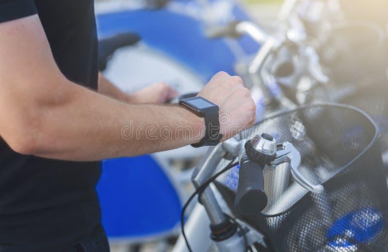 Cyclist che guarda SmartBatch, usando il tracciatore di attività fotografia stock