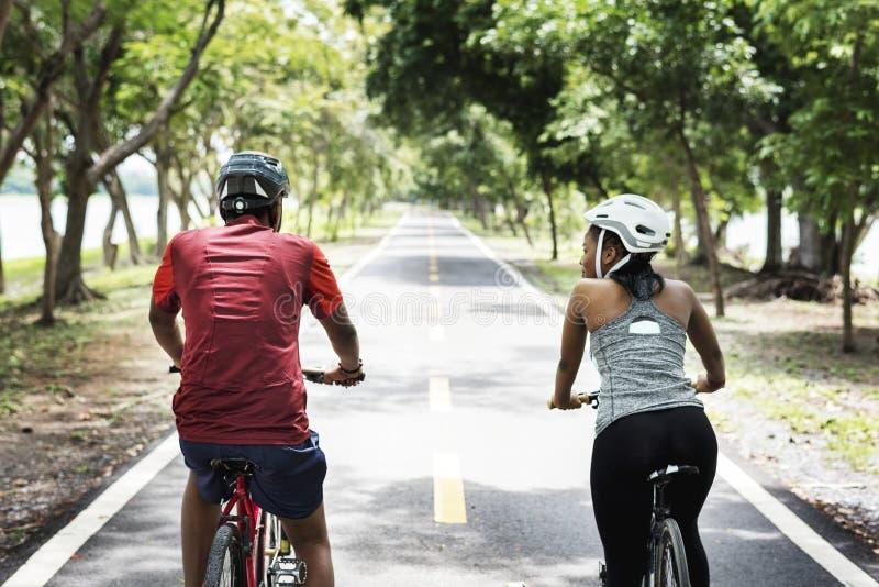 Cyclist couple riding bikes in a park royalty free stock photos