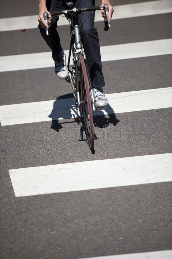 Cyclist crosses the road on pedestrian crossing marked with zebra crossing. A cyclist who prefers a healthy lifestyle crosses the road on a designated pedestrian stock images