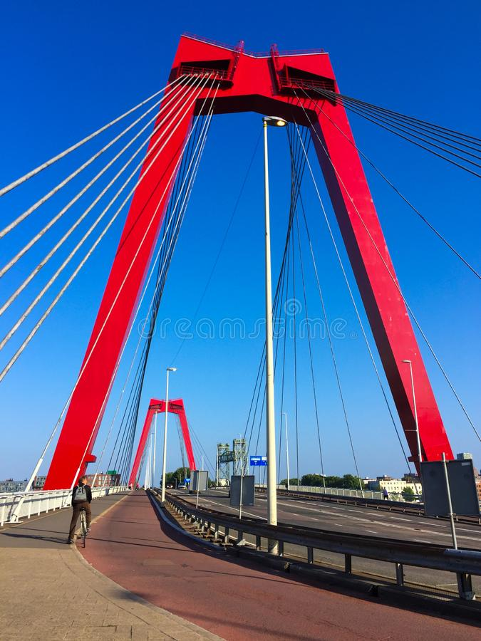 Free Cyclist Crossing The Willemsbrug Bridge Spanning The Nieuwe Maas River In Rotterdam, The Netherlands. Red Bridge Pylons And Cables Stock Images - 138498704