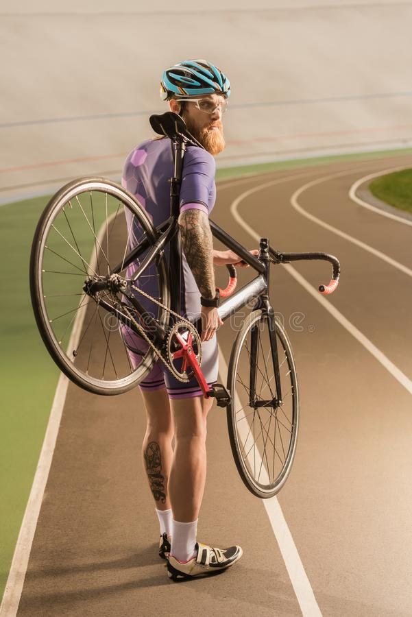 Cyclist on cycle race track. Back view of cyclist with bicycle in hands looking at camera while standing on cycle race track stock image