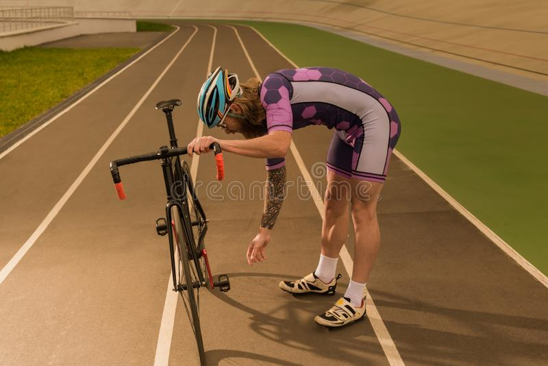 Cyclist on cycle race track. Side view of cyclist checking bicycle wheel while standing on cycle race track stock photo