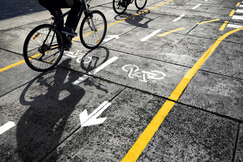 Cyclist on cycle track background. Cyclists following a Cycle track on street. Beautiful sunny day with two cyclist with shadows on cycle track royalty free stock photos