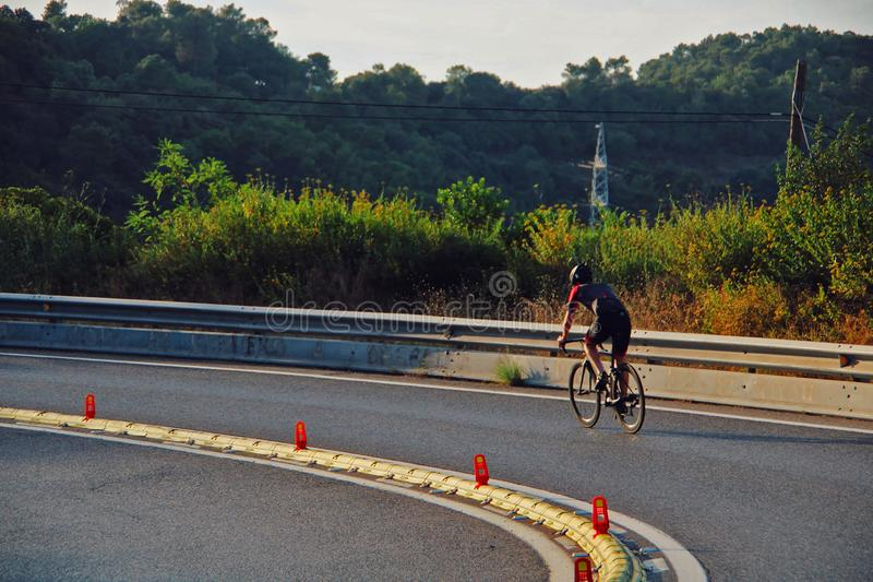 Cyclist driving down a road on the mountain. stock photography
