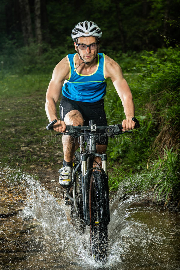 Download Cyclist Driving Through A Streambed Stock Photo - Image: 25686868