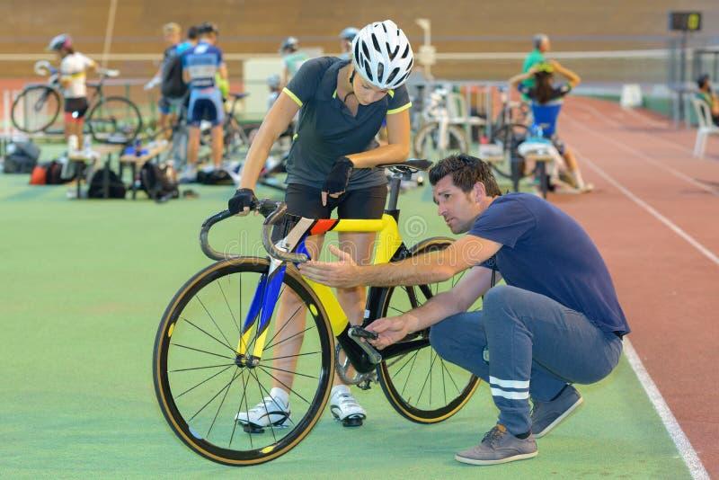 Cyclist e istruttore che guardano la bicicletta immagine stock