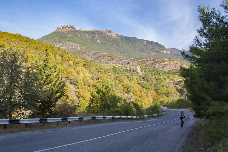 Cyclist on empty asphalt road in the mountains stock photography