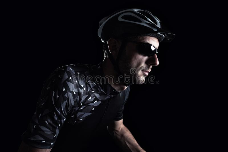 Cyclist in front of a dark background stock images