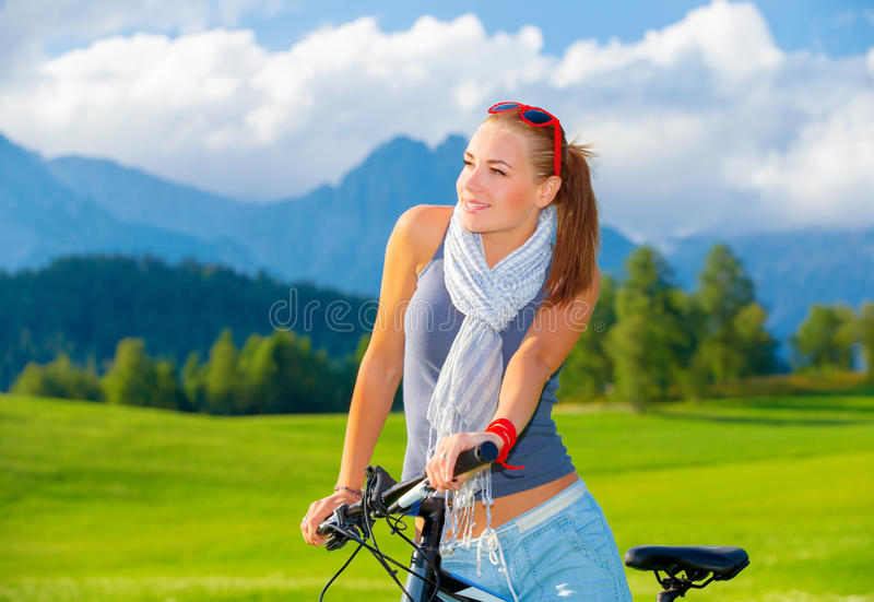 Cyclist girl in mountains. Portrait of cute cyclist girl resting in mountains, traveling on bicycle along Austrian mountains, enjoying beautiful nature, freedom stock photo