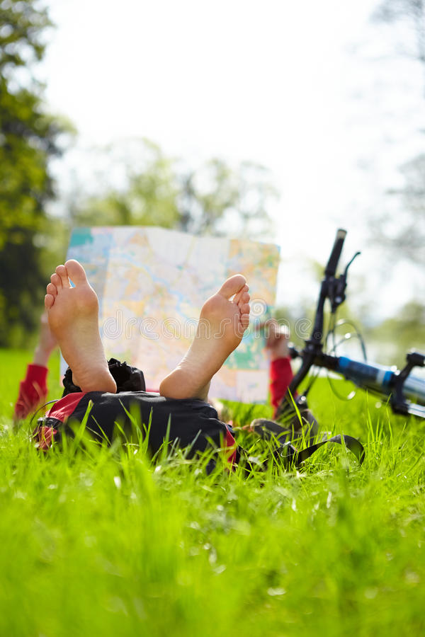 Cyclist on a halt reads a map lying on green grass in spring park. Girl cyclist on a halt reads a map lying on green grass outdoors in spring park. Enjoying stock images