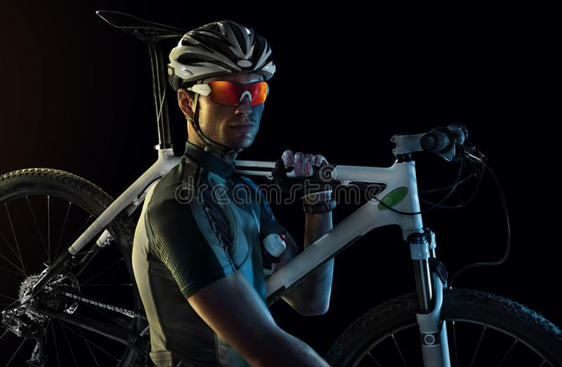 Cyclist carrying bike stock photography
